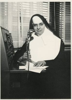 Sister Perpetua sits ready to relay the morning announcements to the Mercy community over the PA.